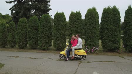 robogó : Young couple hugging on scooter outdoors. Shot on drone