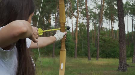 sıkmak : Young girl draving arrow and shooting target Stok Video