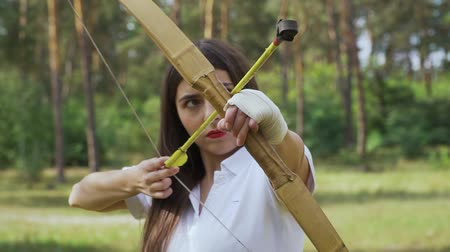 затянуть : Girl archer moving bow between targets and shoots
