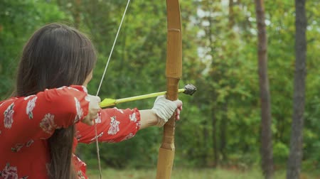 sıkmak : Beautiful girl aims and shoots with a bow. Close-up. Stok Video