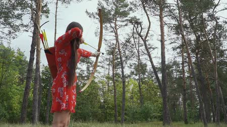 затянуть : Girl is trying to hit an arrow in a tree