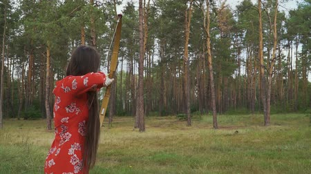 dardo : Woman in red dress practice in shooting in forest