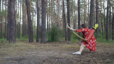 combate : oung girl in red dress shooting from a sitting position
