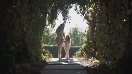 daleko : Mom and daughter in a tunnel of bushes