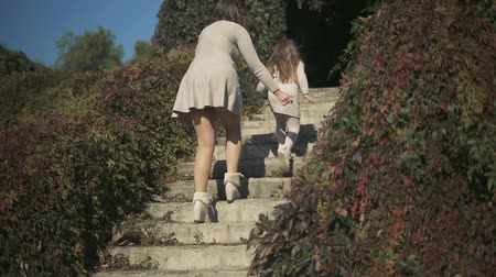 benzer : Small girl and her mom climb the stairs outside. Slow motion