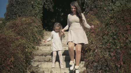 benzer : Mom and daughter go down the stairs in the park. Slow motion Stok Video