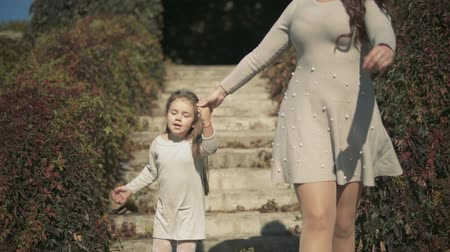 benzer : Gorgeous mom and beautiful daughter go down the stairs in the park. Slow motion