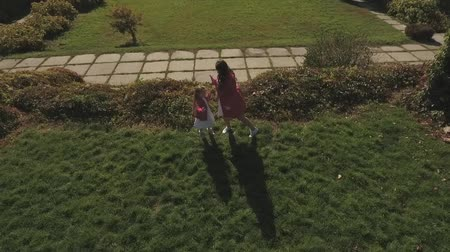 benzer : Mom and daughter dance at the park. Shot on drone