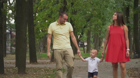 pregnancy : Parents hold the boys hands and walk in the park