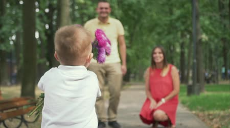 acariciando : Little boy runs with flowers to his parents