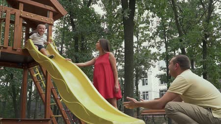 acariciando : Father catches a child from a childrens slide Vídeos
