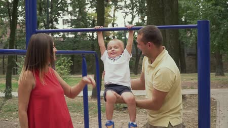 acariciando : Parents swing a child on the bar in the park