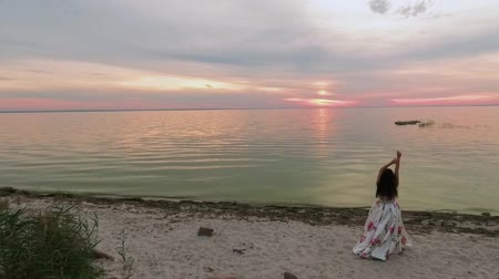 liberal : Young girl in a long dress with arms raised on the river. Shot on drone