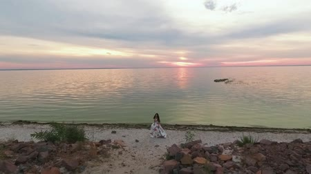 darling : Lovely girl in a beautiful dress walks by the river. Shot on drone