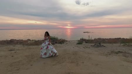 liberal : Beautiful girl in a long evening dress walks by the river. Shot on drone