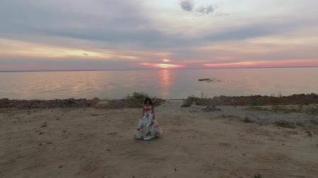 darling : Young girl in a long dress walks along the shore. Shot on drone