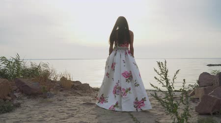 liberal : Cute girl in a long beautiful dress walks by the river
