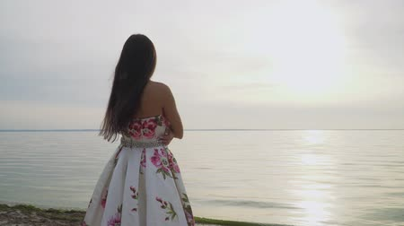 liberal : Brunette in long dress standing by the river