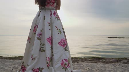 liberal : Charming brunette in a long evening dress standing by the river