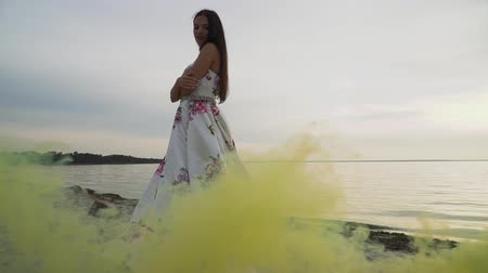 darling : Young girl in evening dress on the background of smoke bombs Stock Footage