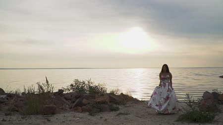 liberal : Tender girl in a long beautiful dress walks along the river bank