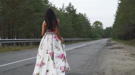 darling : Charming girl in evening dress walks on the road outdoors Stock Footage