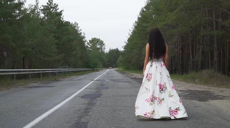 liberal : Pretty girl in a long beautiful dress walks on the road