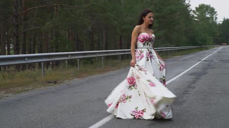 liberal : Beautiful girl in a long dress is spinning on the road