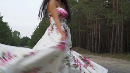 liberal : Tender girl in a long dress is spinning on the road Stok Video
