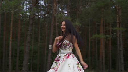 darling : Beautiful girl in a long dress is spinning against the background of the forest