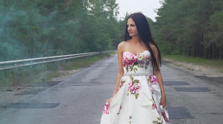liberal : Charming girl in a long dress walks in color smoke
