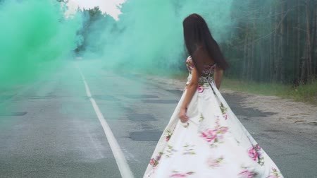 seductive : Lovely girl in a long dress is spinning in the color smoke Stock Footage