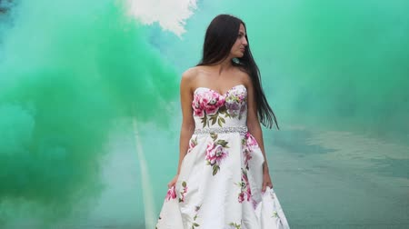 liberal : Darling girl in a long dress walks in color smoke