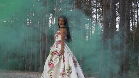 darling : Sweet girl in a dress walks in color smoke against the background of the forest