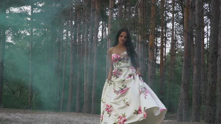 darling : Brunette in a dress walks in color smoke against the background of the forest