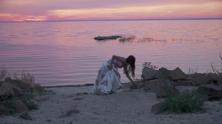 darling : Sweet young girl in a long dress walks along the bank of the river Stock Footage