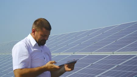 fenntartható : Man taking notes in the tablet on a solar power plant Stock mozgókép