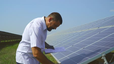 enviroment : Male expert cheking solar panels