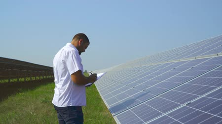 enviroment : Man holding records of solar panels