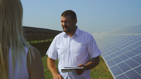enviroment : Man and woman talking at solar power plant