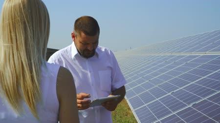 возобновляемый : Couple talking at solar power plant