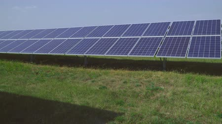enviroment : Solar panels stand in rows on the field.