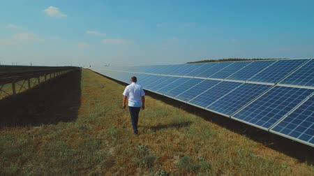 sustainable resources : Engineer walking along solar panels Stock Footage