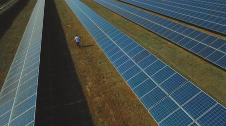 enviroment : Man walking at solar power plant. Shot on drone