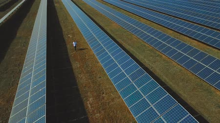 enviroment : Man walking at solar energy station. Shot on drone