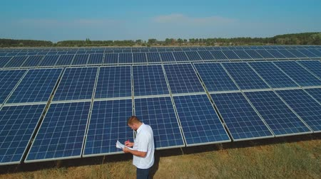 enviroment : Man working at solar power station on meadow. Shot on drone Stock Footage