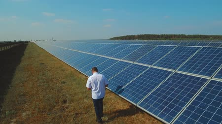 enviroment : Man checking photovoltaic panels. Shot on drone