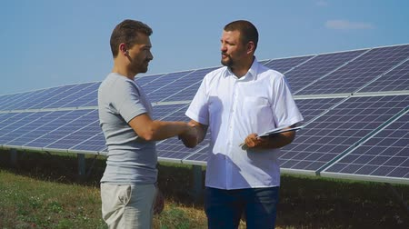 sustainable resources : Two business people shaking hands on the background of solar cells Stock Footage