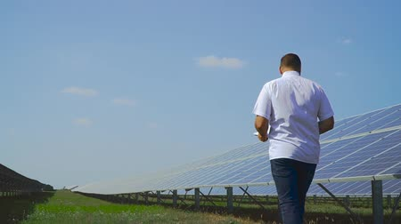 enviroment : Man walking along the solar panel