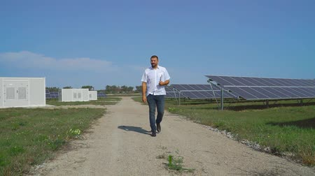 enviroment : Businessman inspects solar panels.